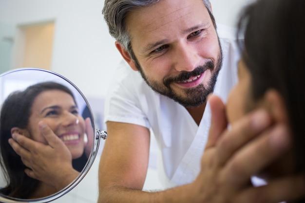 Médico verificar a pele do paciente após tratamento cosmético Foto gratuita