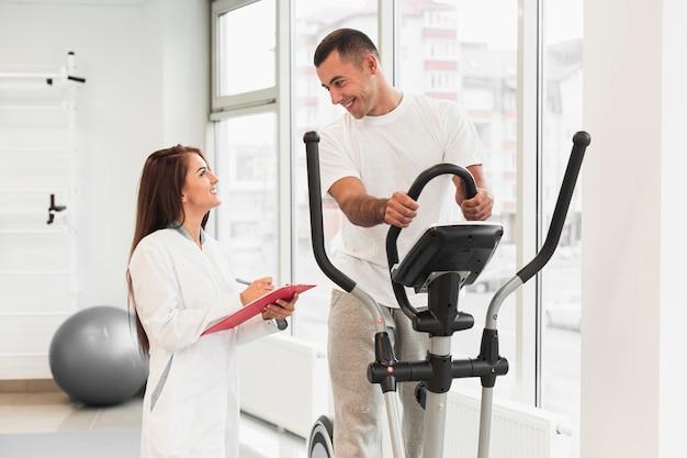 Médico verificar paciente fazendo exercícios Foto gratuita