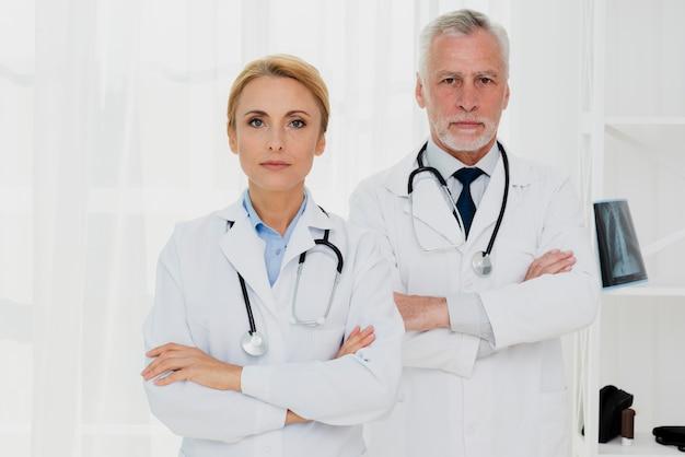Médicos com as mãos cruzadas, olhando para a câmera Foto gratuita