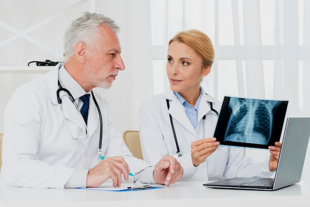 Médicos consultando sobre raio-x Foto gratuita