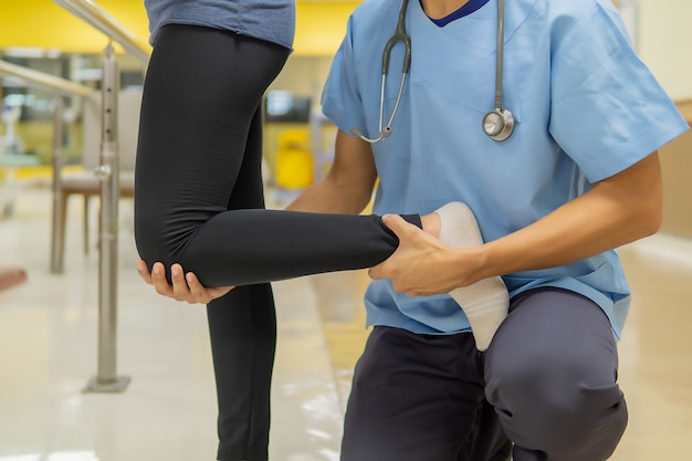 Médicos do sexo masculino estão ajudando pacientes do sexo feminino a exercer no ginásio Foto Premium