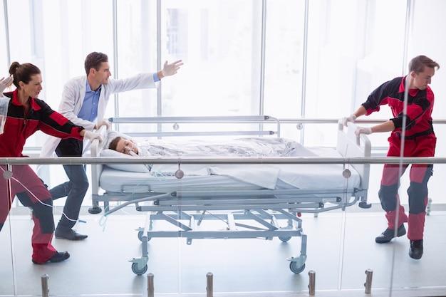 Médicos empurrando cama maca de emergência no corredor Foto gratuita