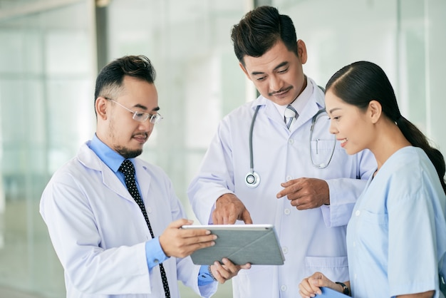 Médicos lendo dados no tablet digital Foto gratuita