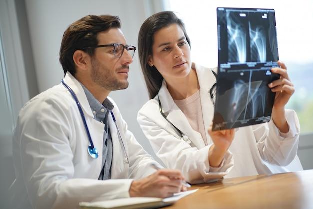 Médicos masculinos e femininos, passando por resultados do paciente Foto Premium