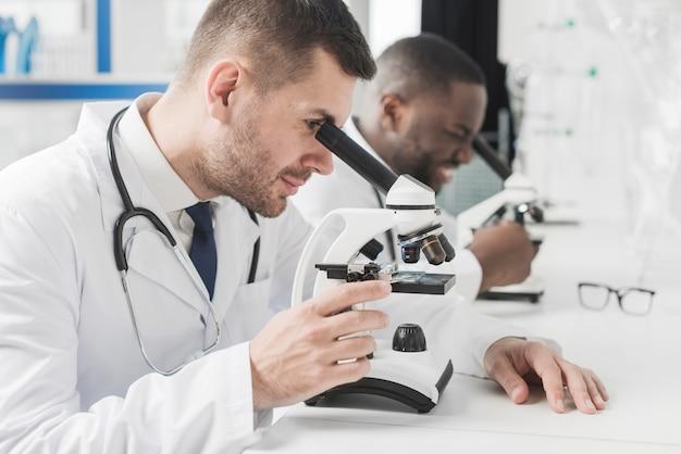 Médicos multiraciais alegres com microscópios Foto gratuita