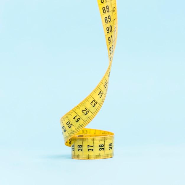 Medida de fita amarela sobre fundo azul Foto gratuita