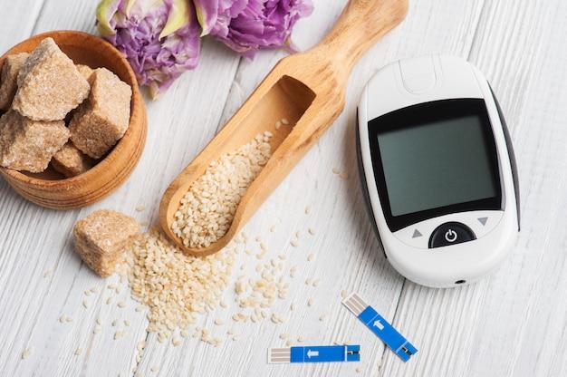 Medidor de glicose, sementes de gergelim e açúcar mascavo Foto Premium