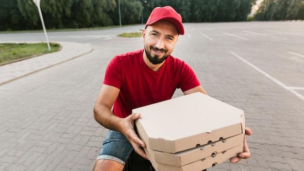 Médio, entrega smiley, sujeito, com, pizza Foto gratuita