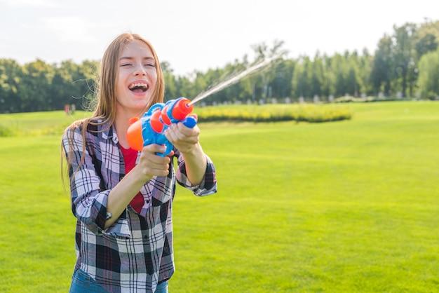 Médio, tiro, alegre, menina, tocando, com, cano de água Foto gratuita