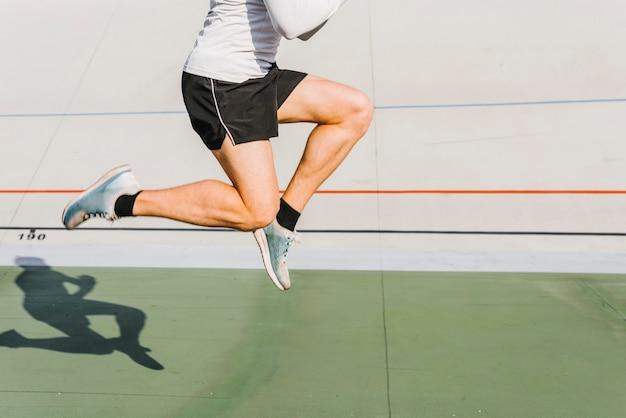 Médio, tiro, atleta, pular, durante, seu, treinamento Foto gratuita