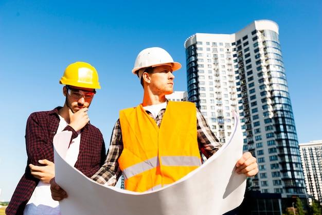 Médio, tiro, baixo, ângulo, vista, engenheiro, arquiteta, olhar, planos Foto gratuita