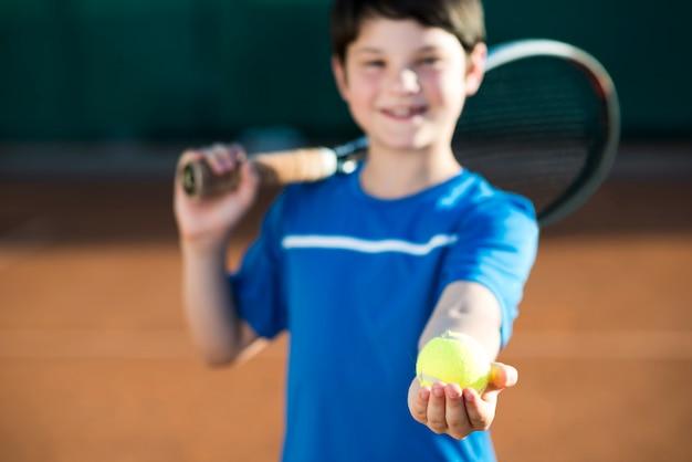 Médio, tiro, criança, segurando, um, bola tênis, em, mão Foto gratuita