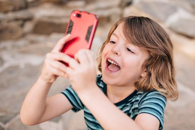 Médio, tiro, criança, tocando, telefone Foto gratuita