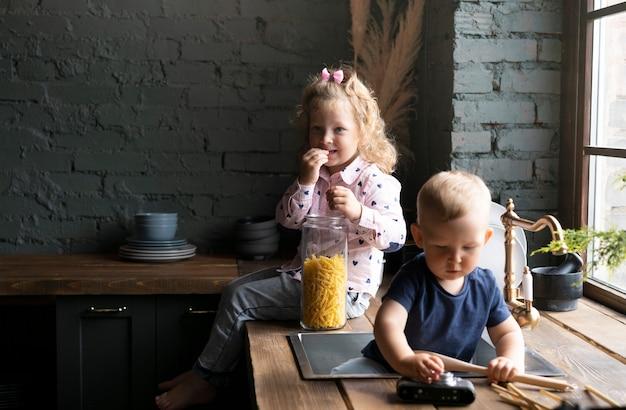 Médio, tiro, crianças, sentando, cozinha Foto gratuita