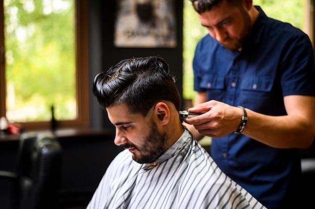 Médio, tiro, de, barbeiro, dar, cliente, um, novo, penteado Foto gratuita