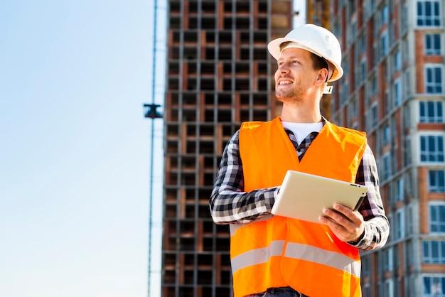 Médio, tiro, engenheiro construção, usando, tabuleta Foto Premium
