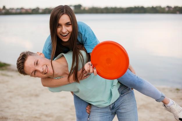 Médio, tiro, feliz, amigos, enganar, ao redor, com, frisbee Foto gratuita