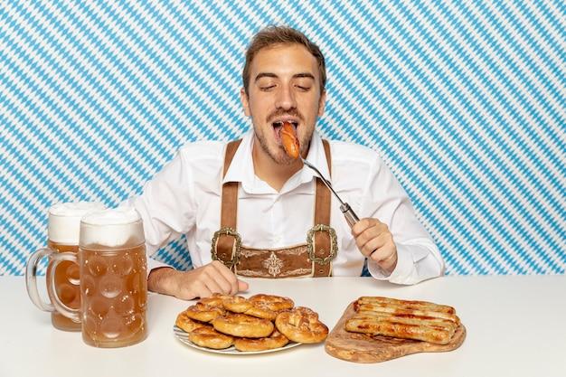 Médio, tiro, homem, comer, alemão, linguiças Foto gratuita