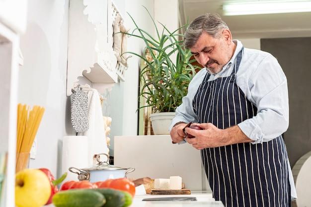 Médio, tiro, homem sênior, cozinhar Foto gratuita