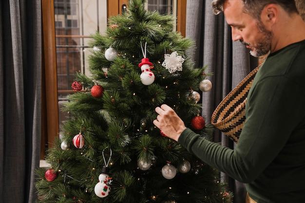 Médio, tiro, homem sênior, decorando, árvore natal Foto gratuita