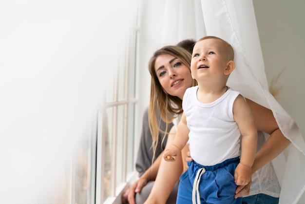 Médio, tiro, mãe, com, filho, perto, a, janela Foto gratuita