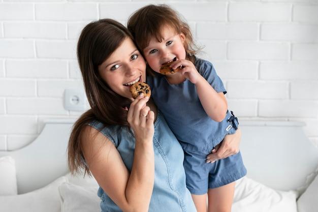 Médio, tiro, mãe filha, comer, chocolate, biscoitos Foto gratuita