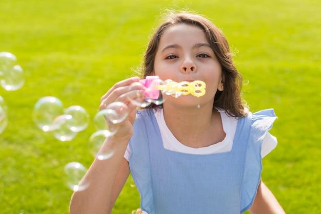 Médio, tiro, menina, fazer, bolhas sabão Foto gratuita
