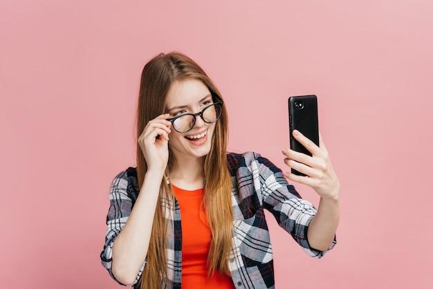 Médio, tiro, mulher, com, óculos, levando, um, selfie Foto gratuita