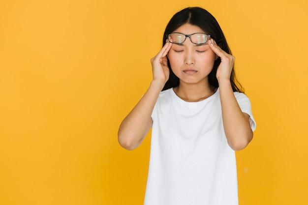 Médio, tiro, mulher jovem, tendo, um, dor de cabeça Foto gratuita