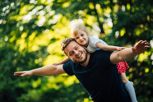 Médio, tiro, pai filha, sorrindo, câmera Foto gratuita