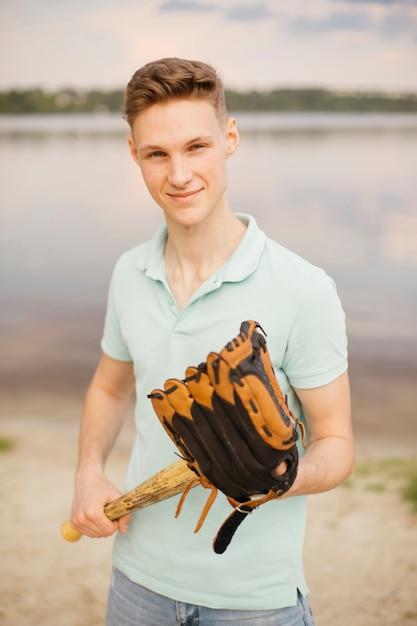 Médio, tiro, smiley, adolescente, com, equipamento baseball Foto gratuita