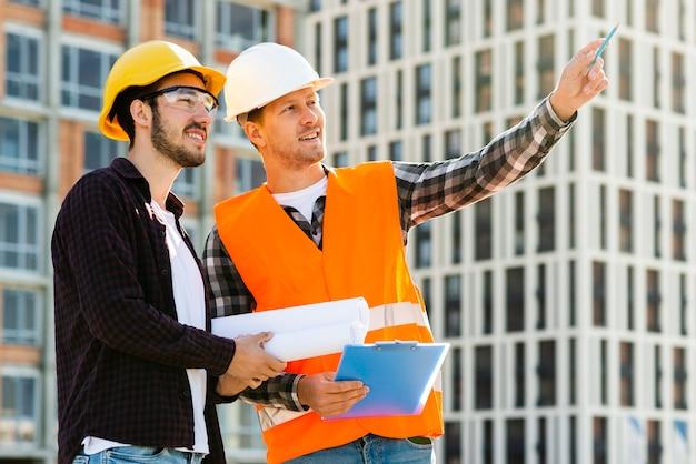 Médio, tiro, vista lateral, de, engenheiro, e, arquiteta, olhar, predios Foto gratuita