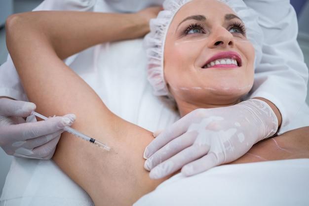 Medique a injeção da mulher em seus poços do braço Foto gratuita