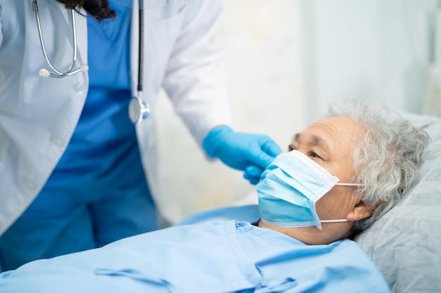 Medique a verificação do paciente sênior asiático da mulher que veste uma máscara protetora para proteger o vírus de coronavirus covid-19. Foto Premium