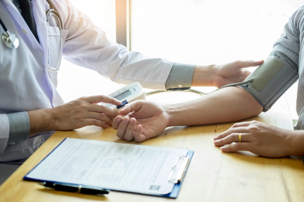 Medique e verificando a pressão sanguínea do paciente no hospital, conceito dos cuidados médicos. Foto Premium