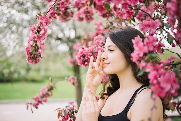 Meditação de mulher bonita com mudra gesto perto de árvore no jardim Foto gratuita