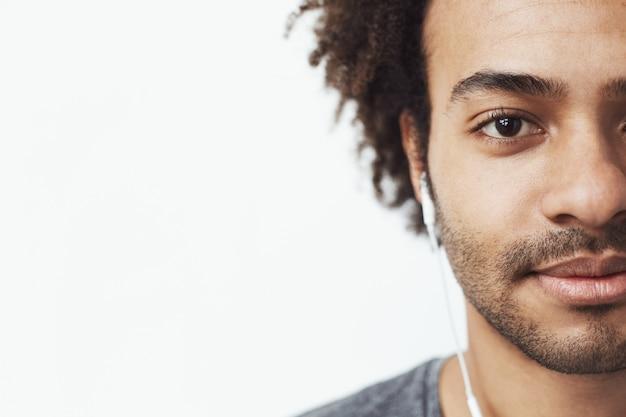 Meia cara fechar retrato do homem africano feliz em fones de ouvido, sorrindo, ouvindo música fumegante. Foto gratuita