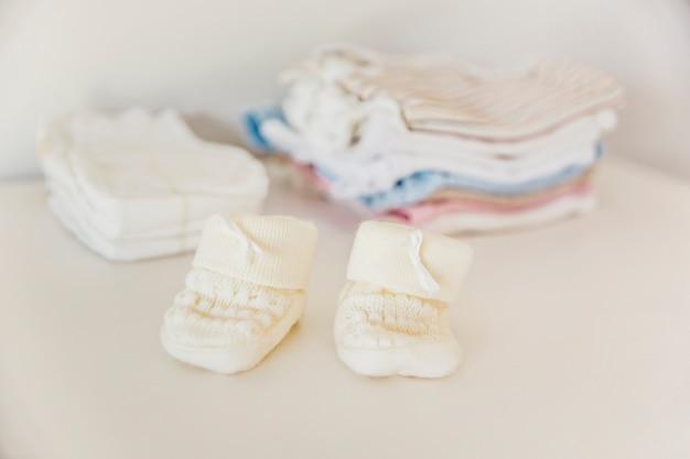 Meia de malha do bebê na frente de fralda e roupas empilhadas Foto gratuita