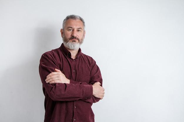 Meia retrato de um homem barbudo grisalho sério em uma camisa de borgonha em um fundo branco Foto Premium