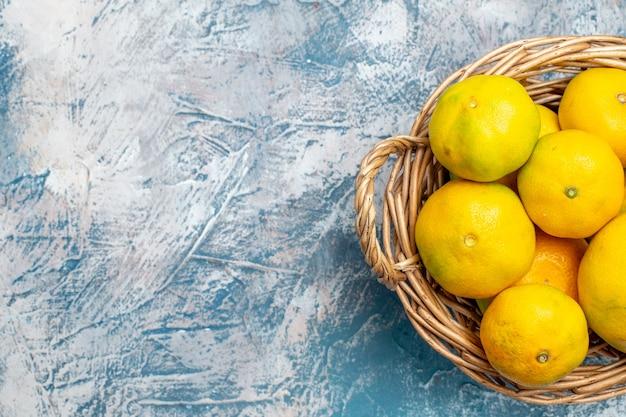 Meia superior vista tangerinas frescas em uma cesta de vime em uma superfície azul e branca com espaço livre Foto gratuita