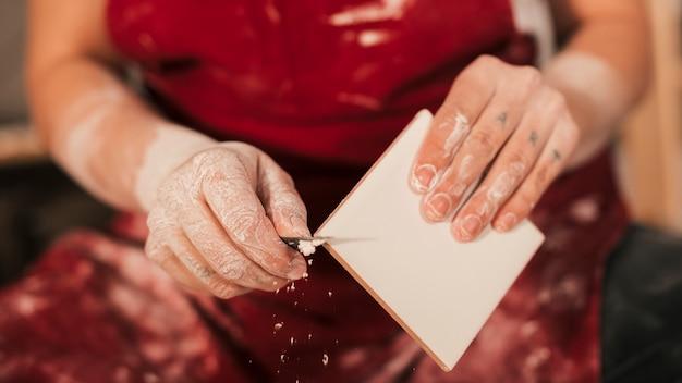 Meio da mão do oleiro feminino removendo a tinta na borda da telha Foto gratuita