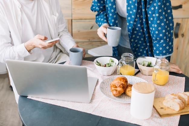 Meio de homens segurando a xícara de café perto delicioso café da manhã com suco e laptop sobre a mesa de madeira Foto gratuita