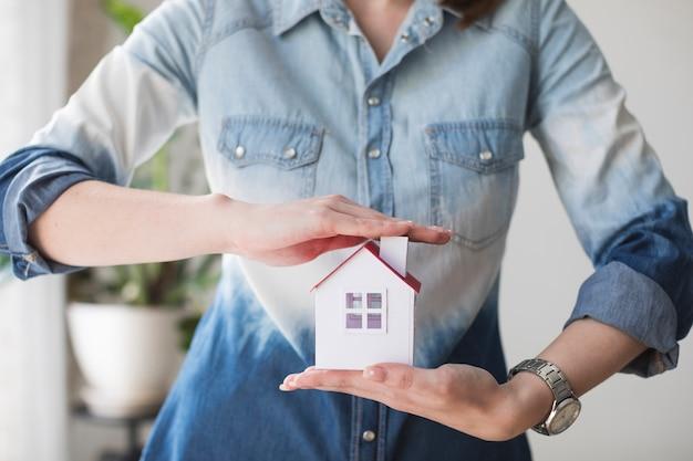 Meio de mulher protegendo o modelo de casa no escritório Foto gratuita