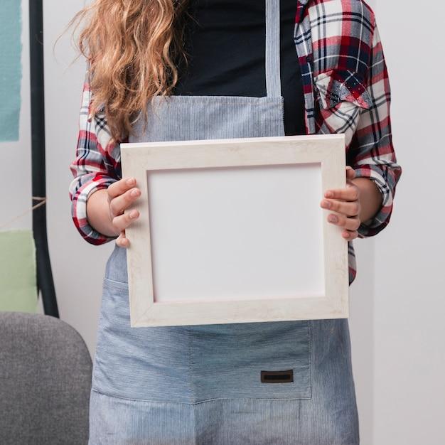 Meio de mulher segurando moldura branca Foto gratuita