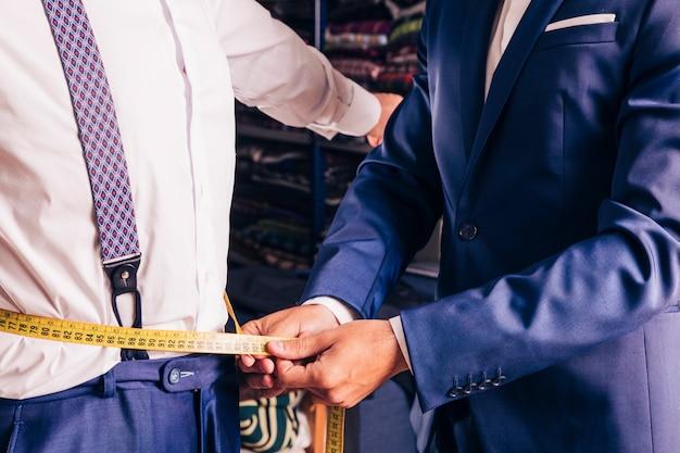 Meio de um alfaiate masculino que toma a medida da cintura do homem Foto gratuita