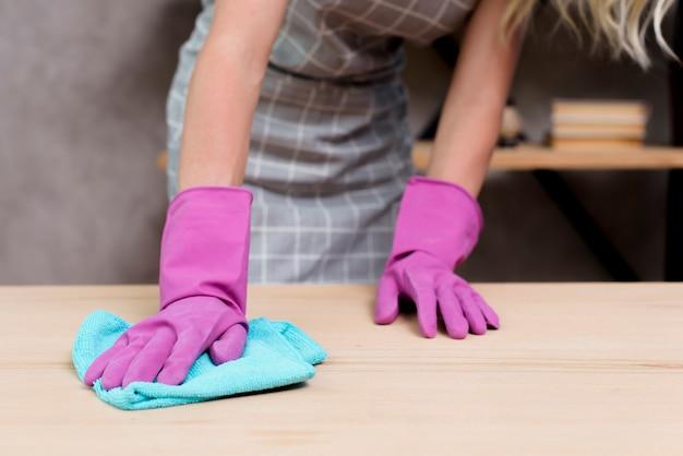 Meio de um faxineiro feminino, limpando a mesa de madeira com pano Foto gratuita