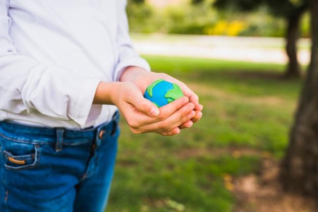 Meio de uma menina segurando o globo nas mãos em concha Foto gratuita