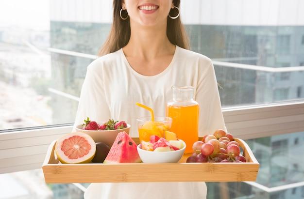 Meio de uma mulher segurando uma bandeja de madeira com muitas frutas e suco Foto gratuita