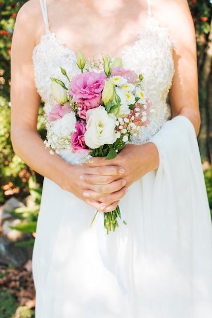 Meio de uma noiva de vestido branco, segurando o buquê de flores nas mãos dela Foto gratuita