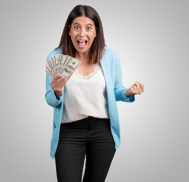 Meio envelhecida mulher muito animada e eufórica, gritando olhando para a frente, comemorando uma vitória e sucesso tendo ganho na loteria, segurando as notas com a mão, conceito de sorte Foto Premium